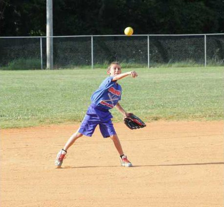 Isaac Lawson goes for the out at first in co-ed softball at Bill page Park last week.
